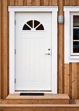 Białe drzwi zewnętrzne w drewnianym domu